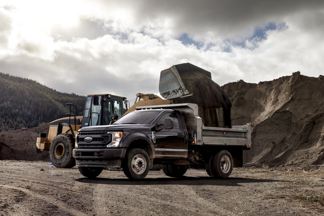 Construction vehicle dumping dirt into back of 2020 Ford Super Duty Chassis Cab with aerial lift upfit