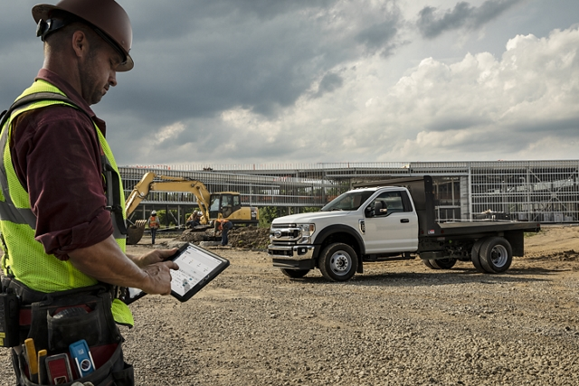 Man looking at tablet near 2020 Ford Super Duty Chassis Cab with upfit parked at construction site