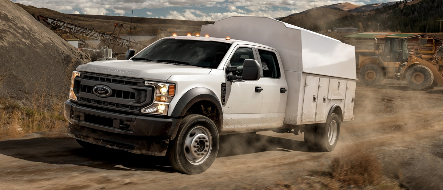 2021 Ford Super Duty Chassis Cab with upfit being driven on dirt road at work site